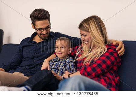 Happy family enjoying watching television together at home.