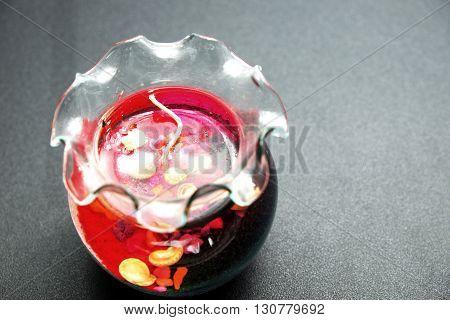 Decorative sea souvenir gel candle on black floor. Focus on surface of gel candle.