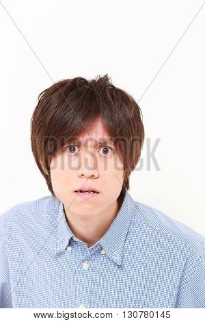 portrait of young Japanese man in a bad mood on white background