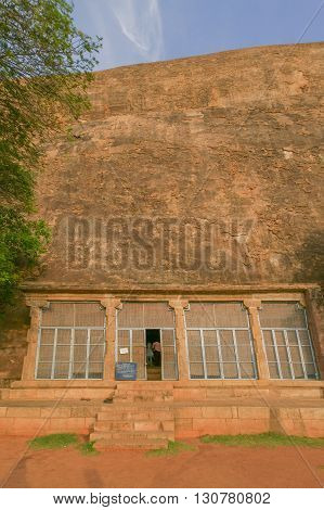 Chettinad India - October 15 2013: Chithannavasal Cave Jain Temple is hewn into a huge rock. A screen fills a pillared gate in front of the cave opening; the only temple item visible from outside. Rock wall in photo.