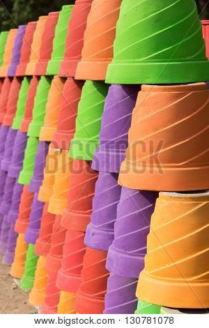 Chettinad India - October 15 2013: wall built with large cement flower pots painted in bright solid colors.