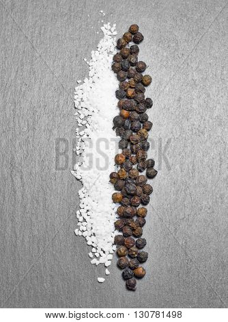 Pepper and salt line on a slate background with copy space. black