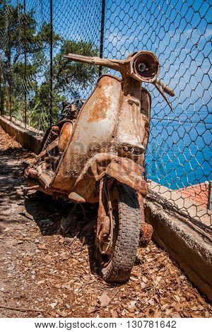 Rusty scooter by the fence on the sea coast