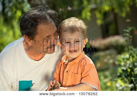 Senior grandfather and two years old grandson play together in the garden, at home.