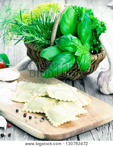 Homemade pasta ravioli with fresh basil on wooden background