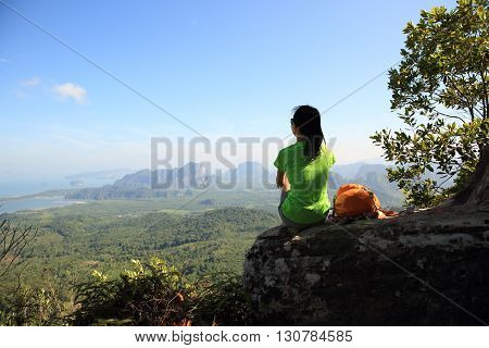 successful woman hiker enjoy the view at mountain peak