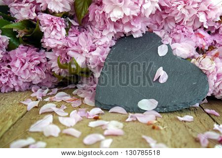 Black slate heart nestled against a pile of pink blossom on a wooden surface. Space for text on heart shape.