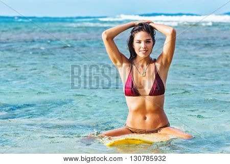 Attractive young female surfer floating upright on surfboard with hands behind head