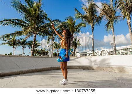 Beautiful Teenage Black Girl In Blue Skirt Take Selfie With Her Smartphone.