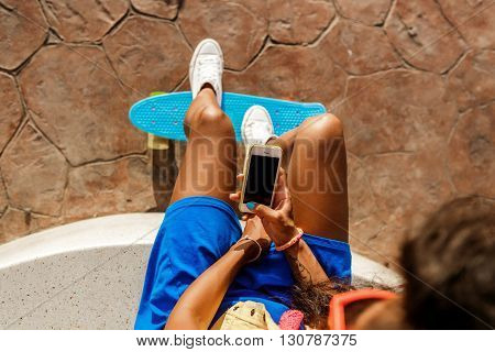 Beautiful Teenage Black Girl In Blue Skirt Sit With Her Smartphone.