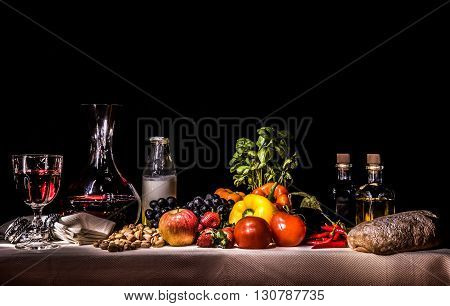 Still light drawing of fruits, vegetables, wine, milk, oil and bread on a dramatic dark background creating a lighting similar to a flemish painting