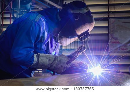 Welding steel structures and bright sparks with lens flare  in factory