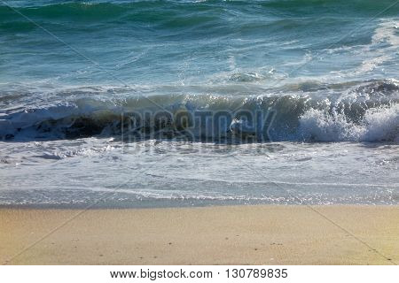 Wet yellow sand flattened by powerful rolling ocean waves