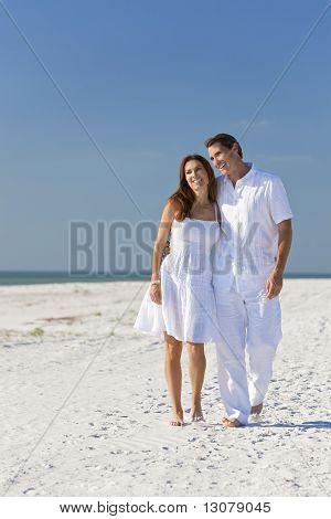 Pareja romántica caminando por una playa vacía