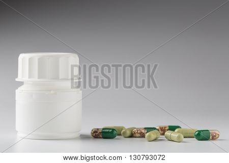 Medicine white bottle and various colorful medical pills and capsules on gray background