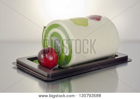 Fancy soap in cake form with cherry on stainless board