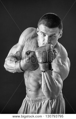 The man in boxing gloves. Young Boxer fighter over black background. Boxing man ready to fight. Boxing workout muscle strength power - the concept of strength training and boxing