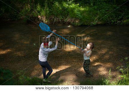 little boy wants to hit a net on girl