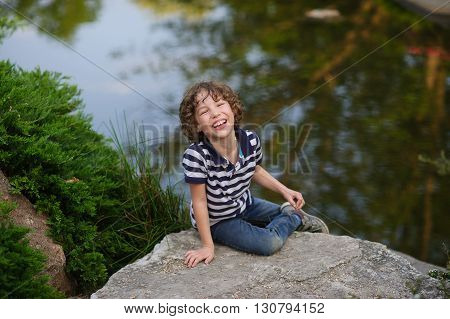 The boy in the striped shirt sits on a rock in a pond. He was a lot of fun. Behind boy beautiful small pond.