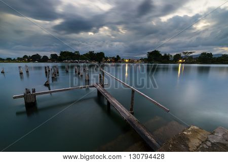 Old and damaged wooden jetty on Poso Lake at Tentana village central Sulawesi Indonesia. Blurred motion dramatic cloudscape long exposure in the blue hour.
