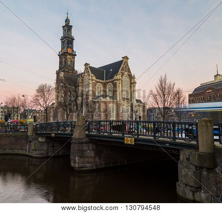 The outside of Westerkerk church in Amsterdam at sunrise. The blur of traffic can be seen going past