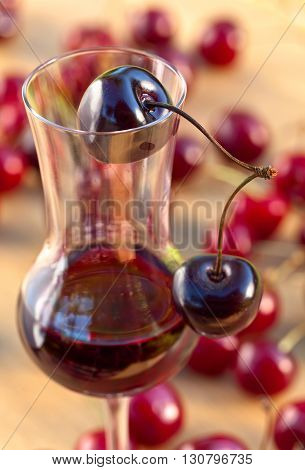glass with cherry liquor and juicy ripe berries
