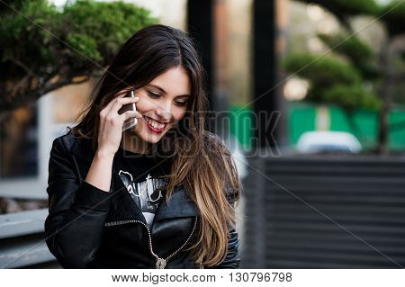 Beautiful woman talking on cellular telephone outdoor.