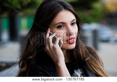 Beautiful businesswoman make call by mobile cell phone. Outdoor, over city