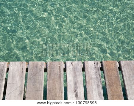Unique perspective wooden slat floor with green crystal sea water surface ripple and sun reflection. Water background. Ocean water texture.