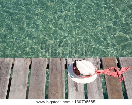 White lady hat and sunglass on wooden slat floor against with green crystal sea water surface ripple and sun reflection. Water background. Ocean water texture.