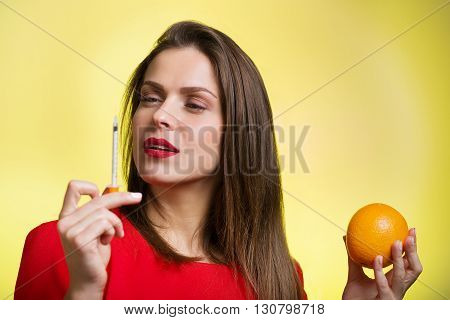 Woman Holding A Syringe And An Orange