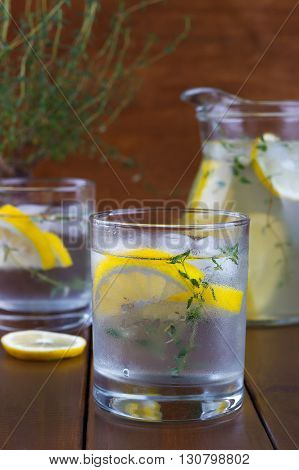 Cool beverage with lemon and thyme, on wooden background