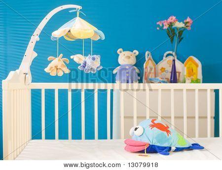 Krippe und weiche Babyspielzeug im Kinderzimmer. Spielzeug gehören offiziell freigegeben.