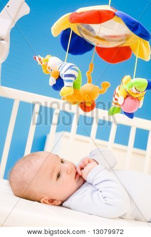 Four months old baby resting on crig at nursery and plying with his little thumb. Toys are officially property released.