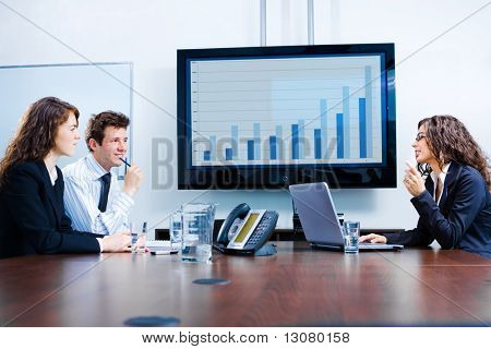 Happy young businesspeople having meeting in boardroom at office in front of a huge plasma TV screen, indoor, smiling.