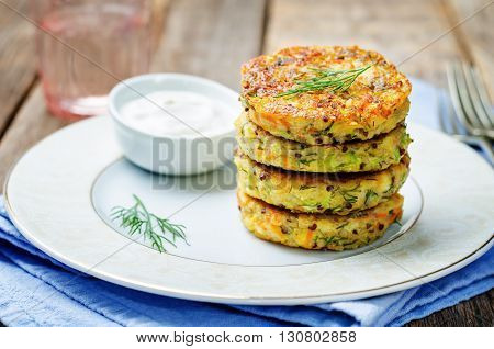 Quinoa Zucchini feta dill fritters on dark wooden background.