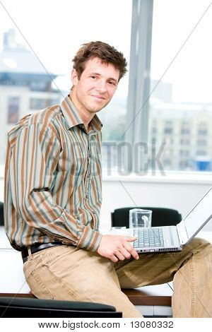 Happy young office worker sitting on table at office and using laptop computer, smiling.