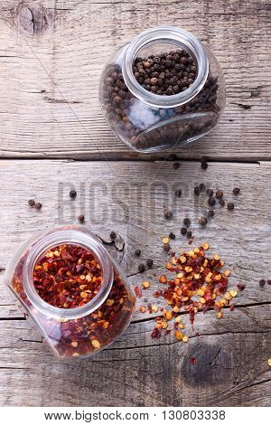 Chili flakes and black pepper in jars on wooden background