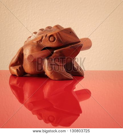 Wooden sculpture of frog on red surfe