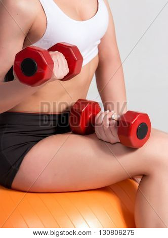 Sportswoman in white top and black shorts with dumbbells exercising on fitball.