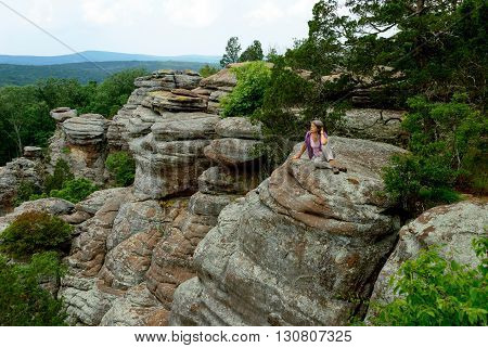 Woman sitting on the edge of a cliff in the Garden of the Gods Wilderness in Shawnee National Forest Illinois USA