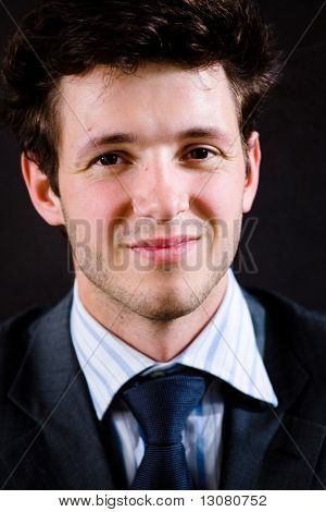 Portrait of happy businessman in suit, smiling.