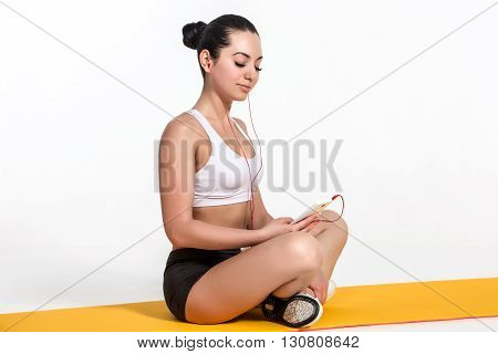 Brunette with fit body on yoga mat. girl with phone and headphones. Healthy lifestyle and sports concept.