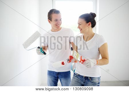 The guy and the girl in jeans and white T-shirts laugh. In the hands of a guy roll. A girl holding a roller and brush
