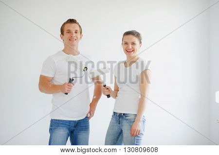 Guy and girl in white t-shirts keep the rollers in their hands. They are smiling on the background of a white wall
