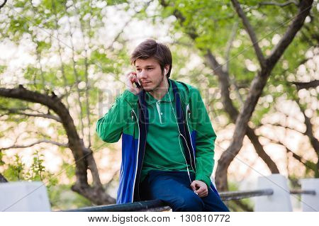 young stylish man sitting and listening to music in the city