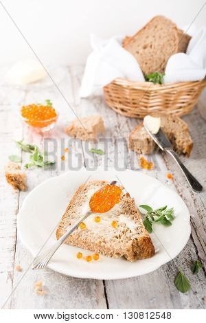 Open sandwich with red caviar and butter, bowl red caviar and fresh baked homemade healthy bread on old white wooden table background. Helthy food.