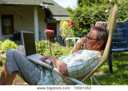 Healthy senior man is his elderly 70s sitting outdoor in garden at home and using laptop computer to browse internet.
