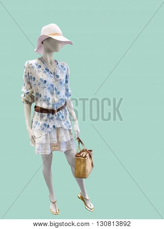Full length female mannequin dressed in fashionable clothes Isolated on green background. No brand names or copyright objects.