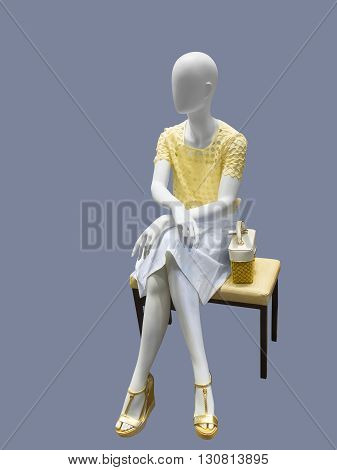 Sitting female mannequin dressed with fashionable modern clothes against gray background. No brand names or copyright objects.